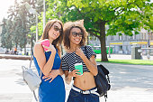 istock Happy girls with take away coffee outdoors 938542726