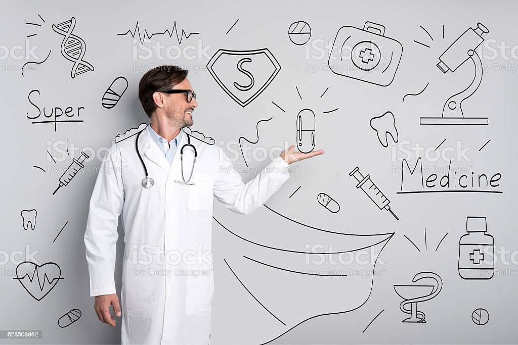 Happy glad doctor standing against painted wall. stock photo