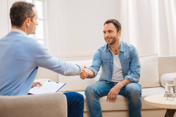 happy glad man shaking hands with psychologist - psychiatrist stock photos and pictures