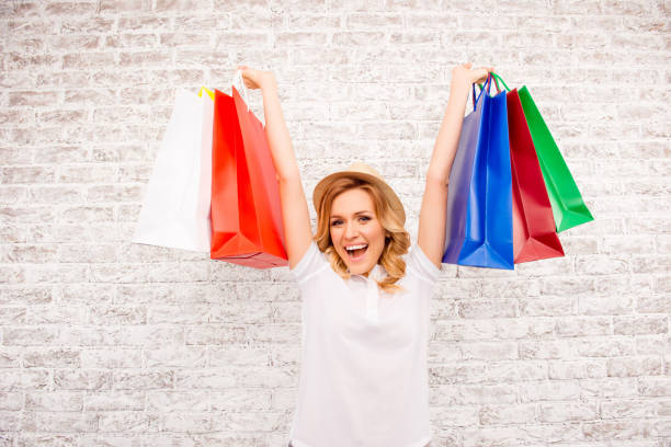 Happy glad woman in hat holding paper bags  with purchases stock photo