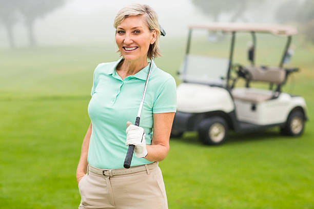 happy golfer with golf buggy behind - female golfer stock photos and pictures