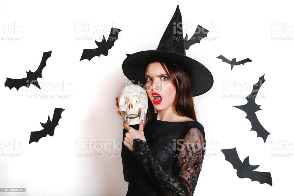 8de35b4ede5 Happy gothic young woman in witch halloween costume with hat standing and  having fun over white