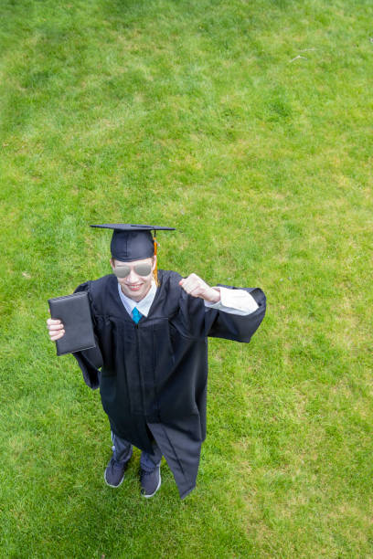happy graduate outdoors holding diploma - sdominick stock pictures, royalty-free photos & images