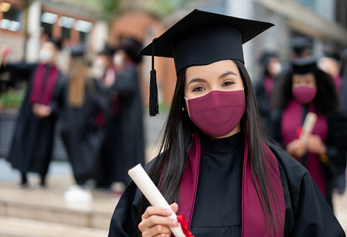 Portrait of a happy graduate student holding her diploma and wearing a facemask at her graduation during the COVID-19 pandemic