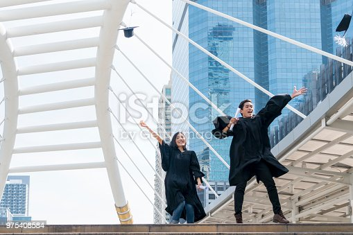 istock happy graduate teen people jumping with the graduation gowns in congratulation ceremony. 975408584