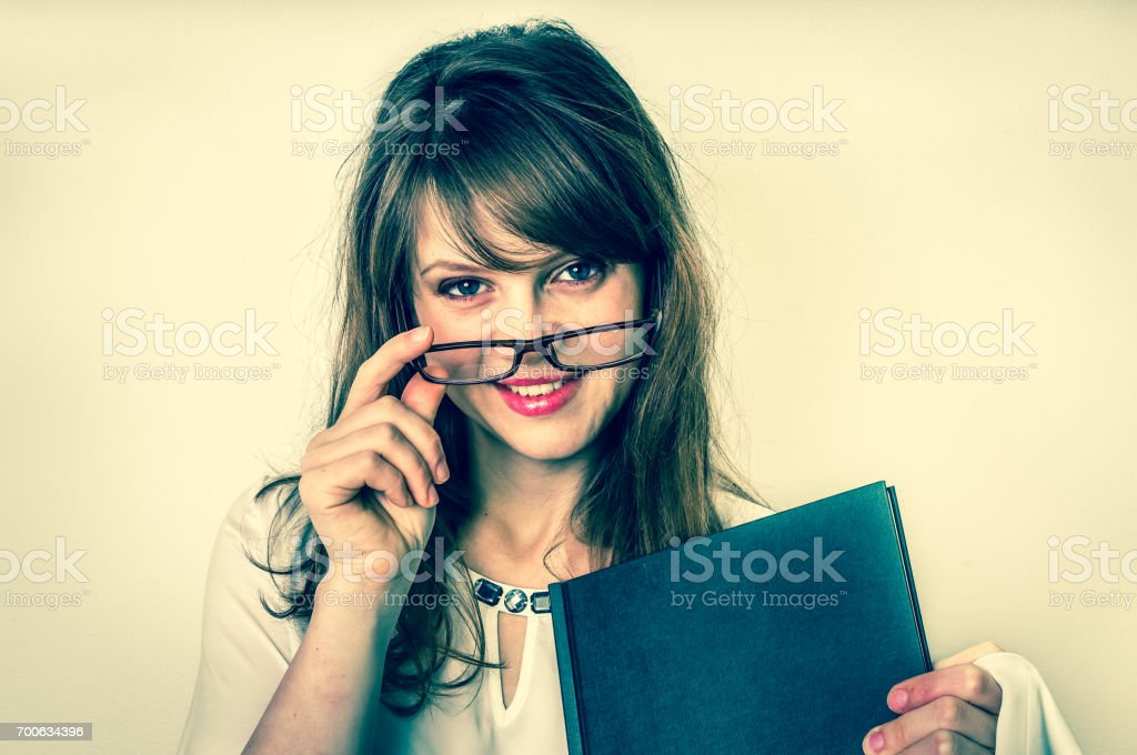 Happy graduate woman with her dissertation work on white stock photo