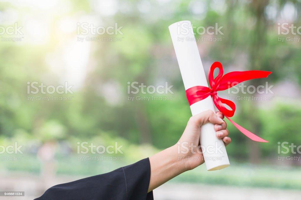 Feliz mujer asiática joven graduada en toga y birrete sostiene un certificado en la mano, concepto de educación - foto de stock
