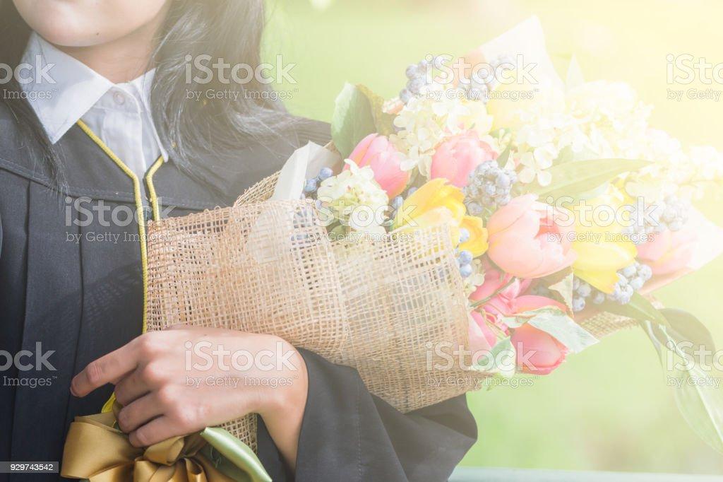 Feliz mujer asiática joven graduada en toga y birrete con ramo y certificado en la mano, concepto de educación - foto de stock