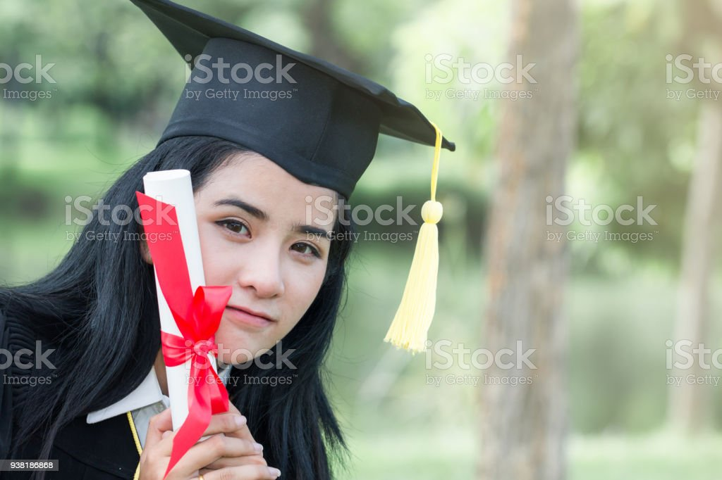 62c9eff53d Happy graduate young Asian woman in cap and gown holding certificate in  hand