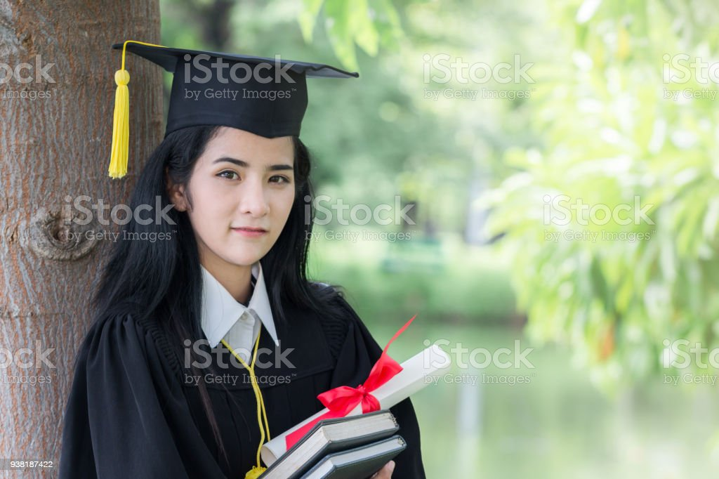 00f63f5a02 Happy graduate young Asian woman in cap and gown holding certificate and  the book in hand