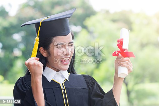 istock Happy graduate young Asian woman in cap and gown holding certificate in hand, Education concept 943811026