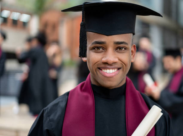 Happy graduating student holding his diploma Portrait of a happy African American graduating student holding his diploma and looking at the camera smiling alumnus stock pictures, royalty-free photos & images