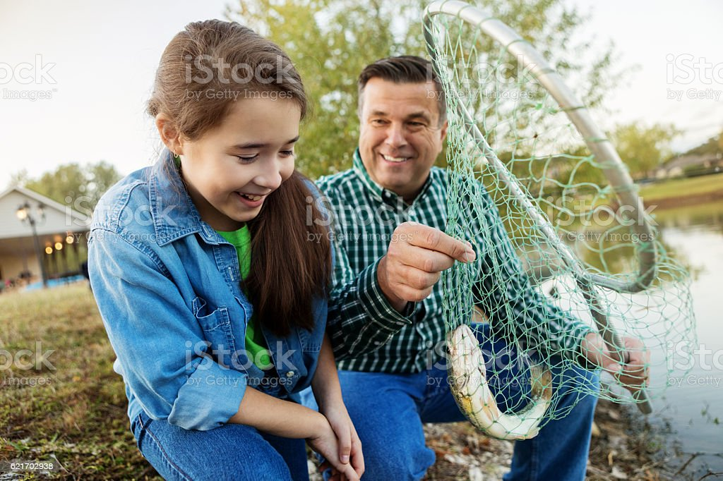 Happy granddaughter and grandfather catch fish in a net stock photo