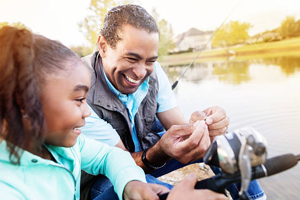 Happy grandfather and granddaughter fish together stock photo