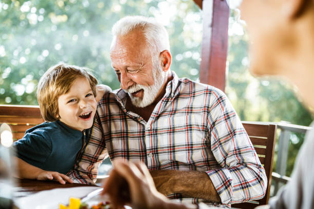 Happy grandfather and grandson having fun during a meal on a terrace. Happy senior man having fun with his small grandson during a meal on a balcony. grandson stock pictures, royalty-free photos & images