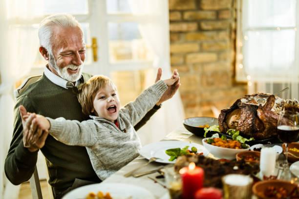 happy grandfather and grandson having fun during thanksgiving lunch at home. - jantar assado imagens e fotografias de stock