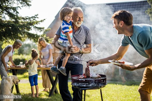 istock Happy grandfather and grandson talking to young father preparing barbecue in the backyard. 1006417374