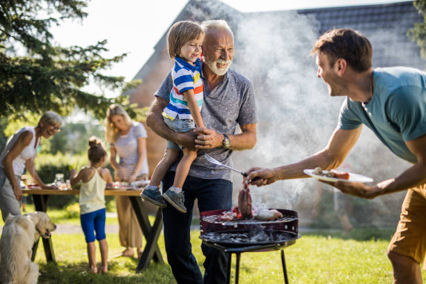 happy grandfather and grandson talking to young father preparing barbecue in the backyard. - barbecue grill stock photos and pictures