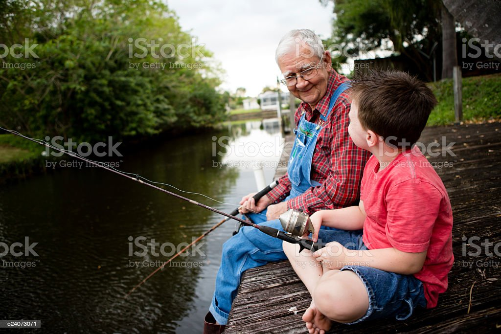 Happy Grandfather and Great Grandson Fishing Together royalty-free stock photo