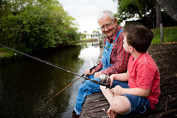 Happy Grandfather and Great Grandson Fishing Together stock photo