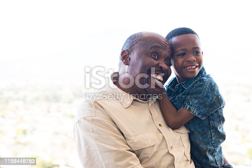 istock Happy grandfather carrying grandson in balcony 1158448783