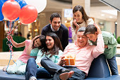 Happy grandfather celebrating Father's Day with his family at the mall and holding a gift while smiling – lifestyle concepts
