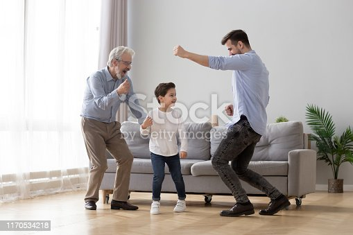 istock Happy grandfather, father and little son having fun, dancing together 1170534218