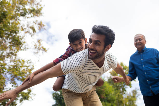 Happy grandfather looking at man giving piggy backing to son Happy grandfather looking at man giving piggy backing to son with arms oustretched in yard indian family stock pictures, royalty-free photos & images