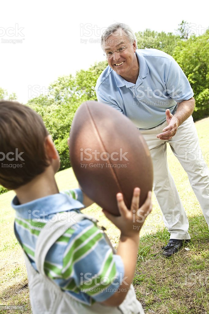 Happy Grandfather Playing Football With His Grandson at the Park royalty-free stock photo