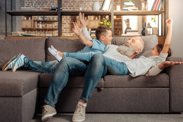 happy grandfather playing with his grandchildren on couch - baby boomers stock pictures, royalty-free photos & images