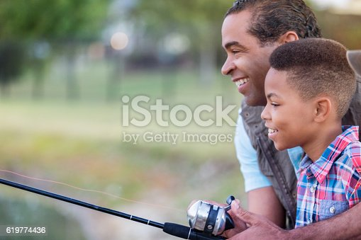 istock Happy grandfather teaches grandson to fish 619774436
