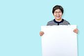白い歯で微笑む幸せなおばあちゃんは、瞬間を楽しみ、空白のボードを保持します。あなたの広告のテキストメッセージやプロモーションコンテンツのための白い空白のボードを示すアジア�