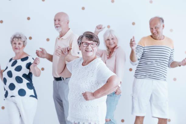 glückliche großmutter tanzen mit freunden - rentenpunkte stock-fotos und bilder