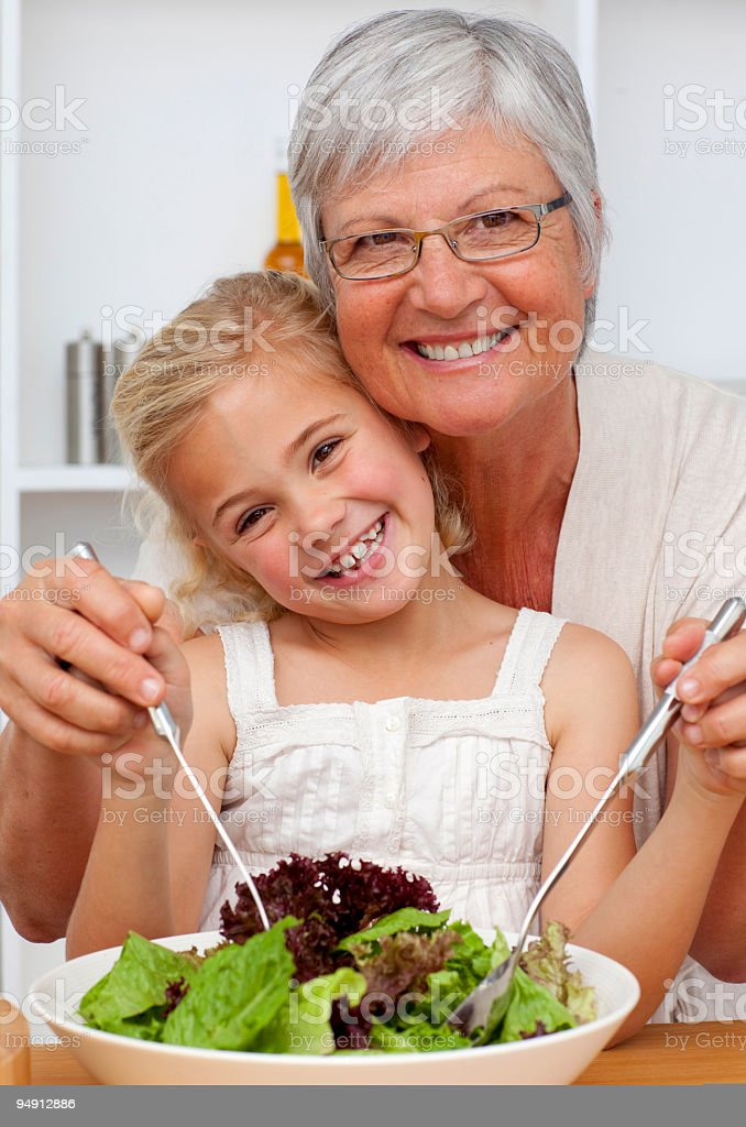 Happy grandmother eating a salad with granddaughter royalty-free stock photo