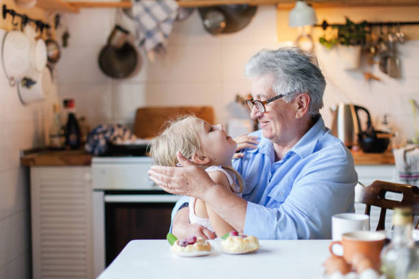 Happy grandmother is hugging child in cozy kitchen at home. stock photo