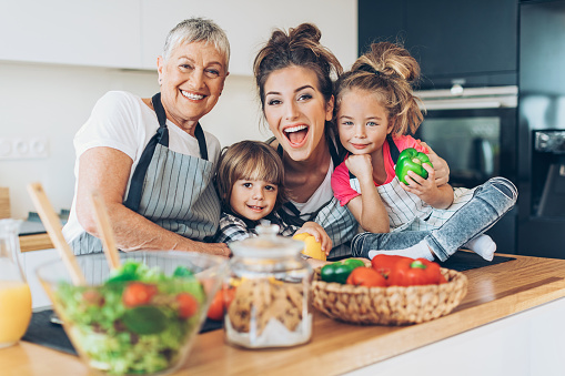 638984280 istock photo Happy grandmother, mother and two children in the kitchen 629553426