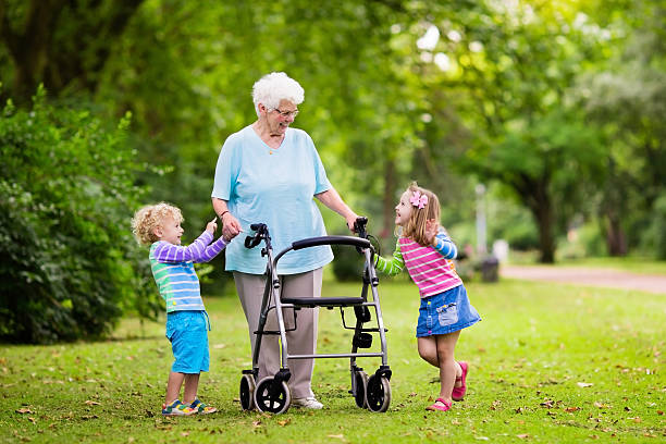 happy grandmother with walker playing with two kids - laufgestell stock-fotos und bilder