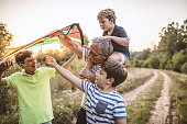 Carefree children and a happy grandpa flying kite in nature