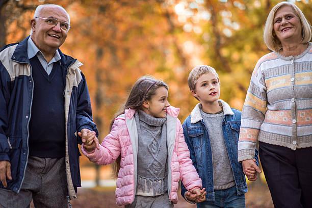 Happy grandparents and grandchildren taking a walk in autumn day. – Foto