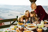 Happy grandparents communicating with their small grandkids during lunch on a balcony. Copy space.