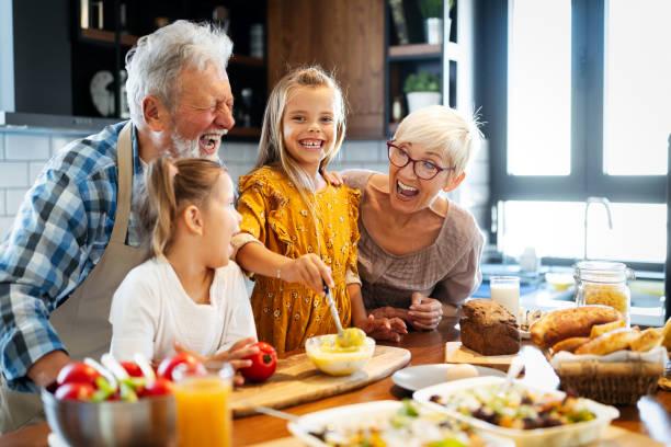 Happy grandparents with grandchildren making breakfast in kitchen stock photo