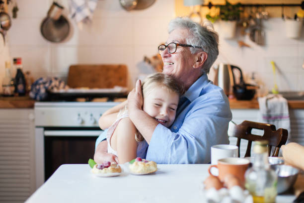 Happy grangmother is hugging granddaughter in cozy home kitchen. Family is cooking together. Senior woman and cute little child girl are smiling. Kid is enjoying kindness, warm hands, care, support. Happy grandmother is hugging granddaughter in cozy home kitchen. Family is cooking together. Senior woman and cute little child girl are smiling. Kid is enjoying kindness, warm hands, care, support. grandmother stock pictures, royalty-free photos & images