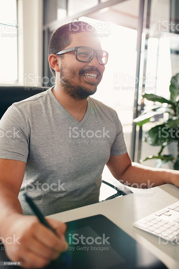 Happy graphic designer working in his office stock photo
