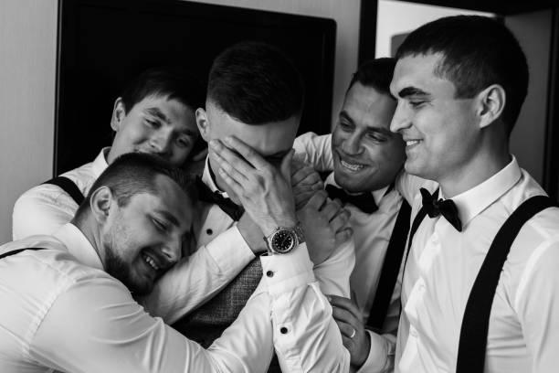 Happy groom and joyful groomsmen embracing after wedding ceremony. Black and white wedding photography stock photo