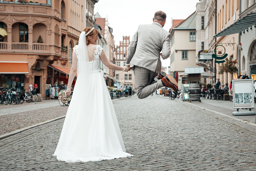 Happy groom jumping in the air on his wedding day