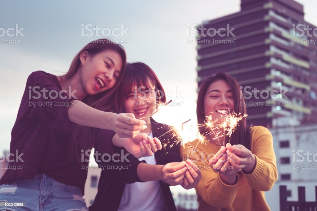 Happy group of asia girl friends enjoy and play sparkler at roof top party at evening sunset,Holiday celebration festive,teenage lifestyle,freedom and fun. stock photo