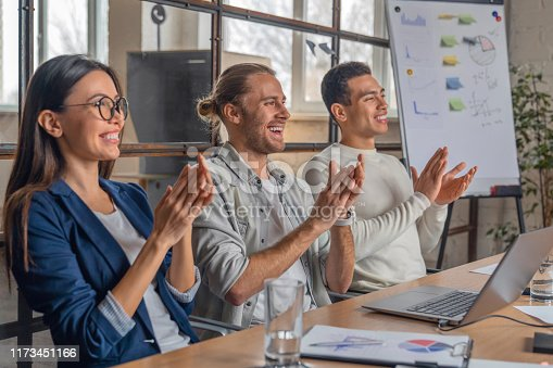 1141929391 istock photo Happy group of businesspeople clapping in office. Young business partners applauding to reporter after listening to presentation at coworking zone 1173451166