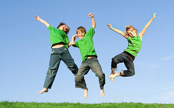happy group of children or kids  jumping for joy - triplets stock photos and pictures