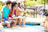 istock Happy group of college kids playing by the pool 582316594