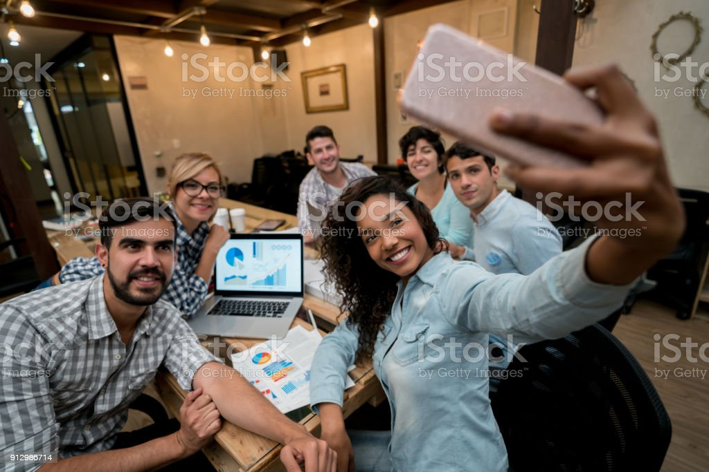Happy group of coworkers taking a selfie at a creative office Portrait of a happy group of Latin American coworkers taking a selfie at a creative office with a cell phone. **DESIGN ON SCREEN AND DOCUMENTS WERE MADE FROM SCRATCH BY US** Adult Stock Photo